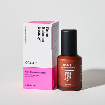 Frosted amber glass bottle and cardboard product box of 004-Br Skin Brightening Cream against light grey background.