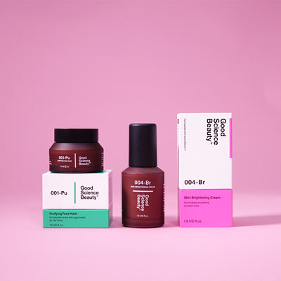 An amber frosted glass jar of 001-Pu Purifying Face Mask placed on top of the corresponding product box and an amber frosted glass bottle of 004-Br Skin Brightening Cream beside the corresponding product box against pink background