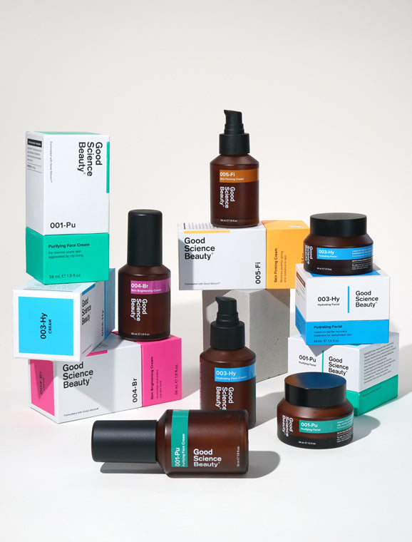 A stack of amber glass bottles and jars and colorful boxes of Good Science Beauty products on a white surface against white background.