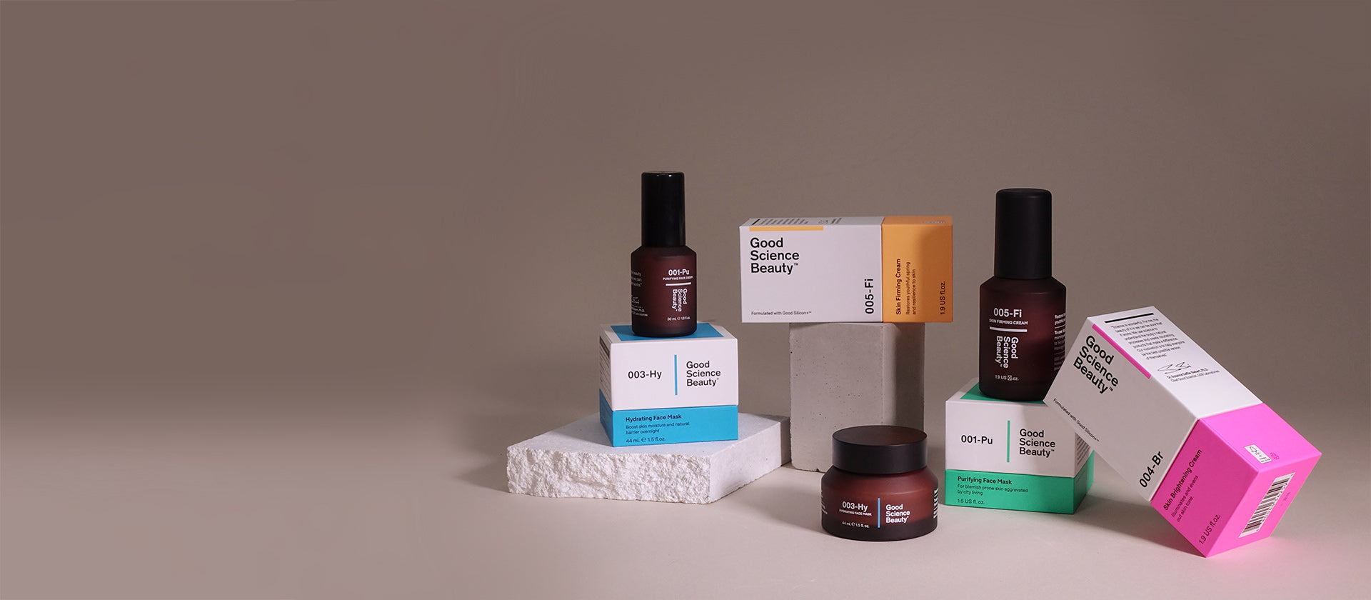 Arrangement of amber frosted glass bottles of Good Science Beauty creams, an amber frosted glass jar of 003-Hy Hydrating Face Mask, and four Good Science Beauty product boxes, each of which consists of a largely white upper section and a brightly coloured lower section