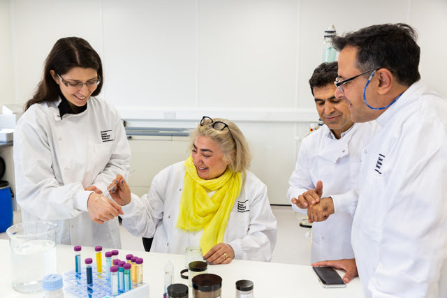 Suzanne Saffie-Siebert sits at lab bench surrounded by three smiling members of her R&D team. She uses a glass pipette to apply a product sample to the hand of a female scientist.