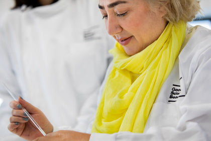 Suzanne Saffie-Siebert in a white lab coat looks down at a glass pipette in her hand.444