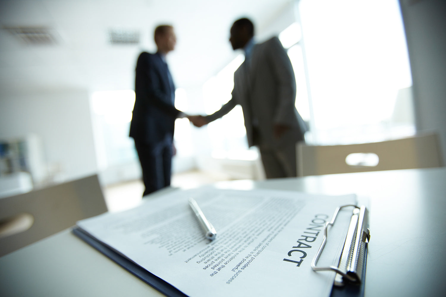 Shaking hands over signed copier lease agreement