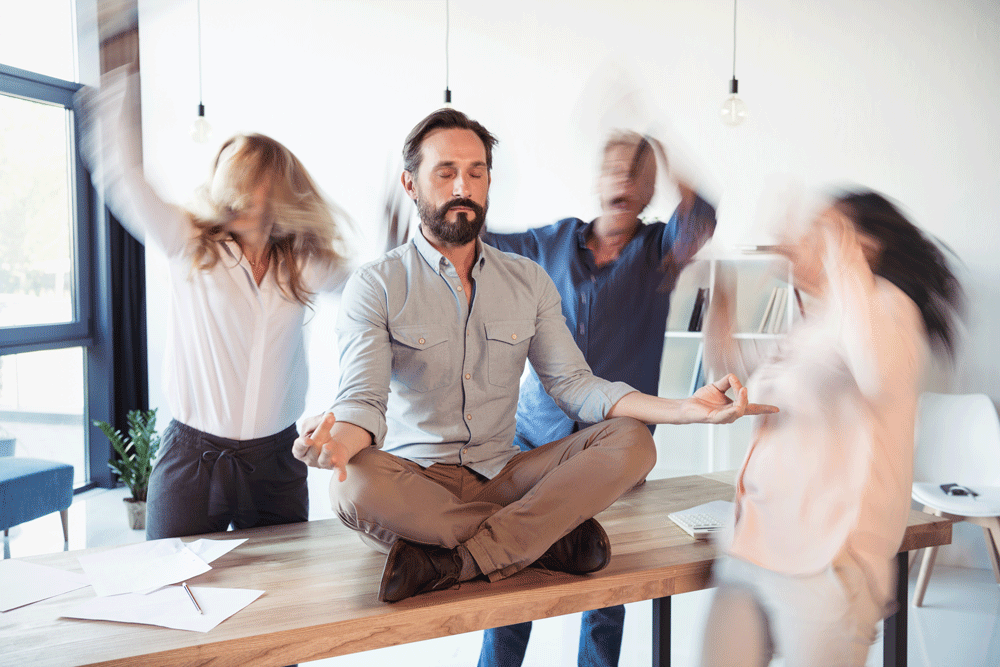 Business owner trying to meditate while team is stressed around him