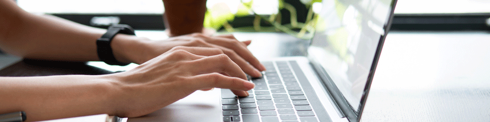Woman working from home and typing on laptop