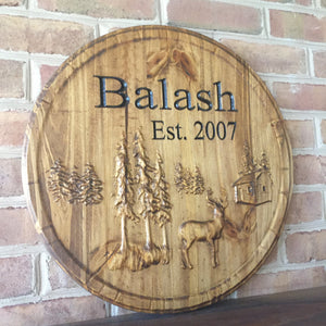 Carved wood sign with trees, deer, cabin, and last name