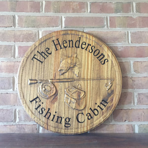 Carved wood sign with fish, rod, and family name