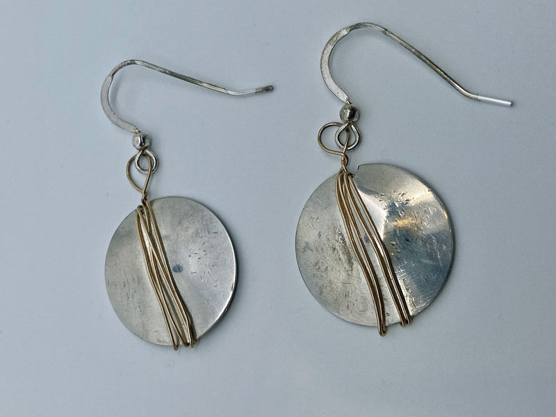 Earrings of hammered sterling silver discs wrapped with gold wire