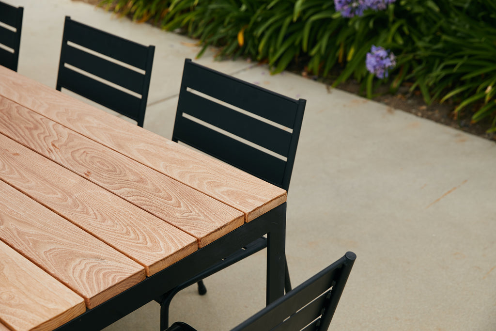 Outdoor dining table with wood top and steel base