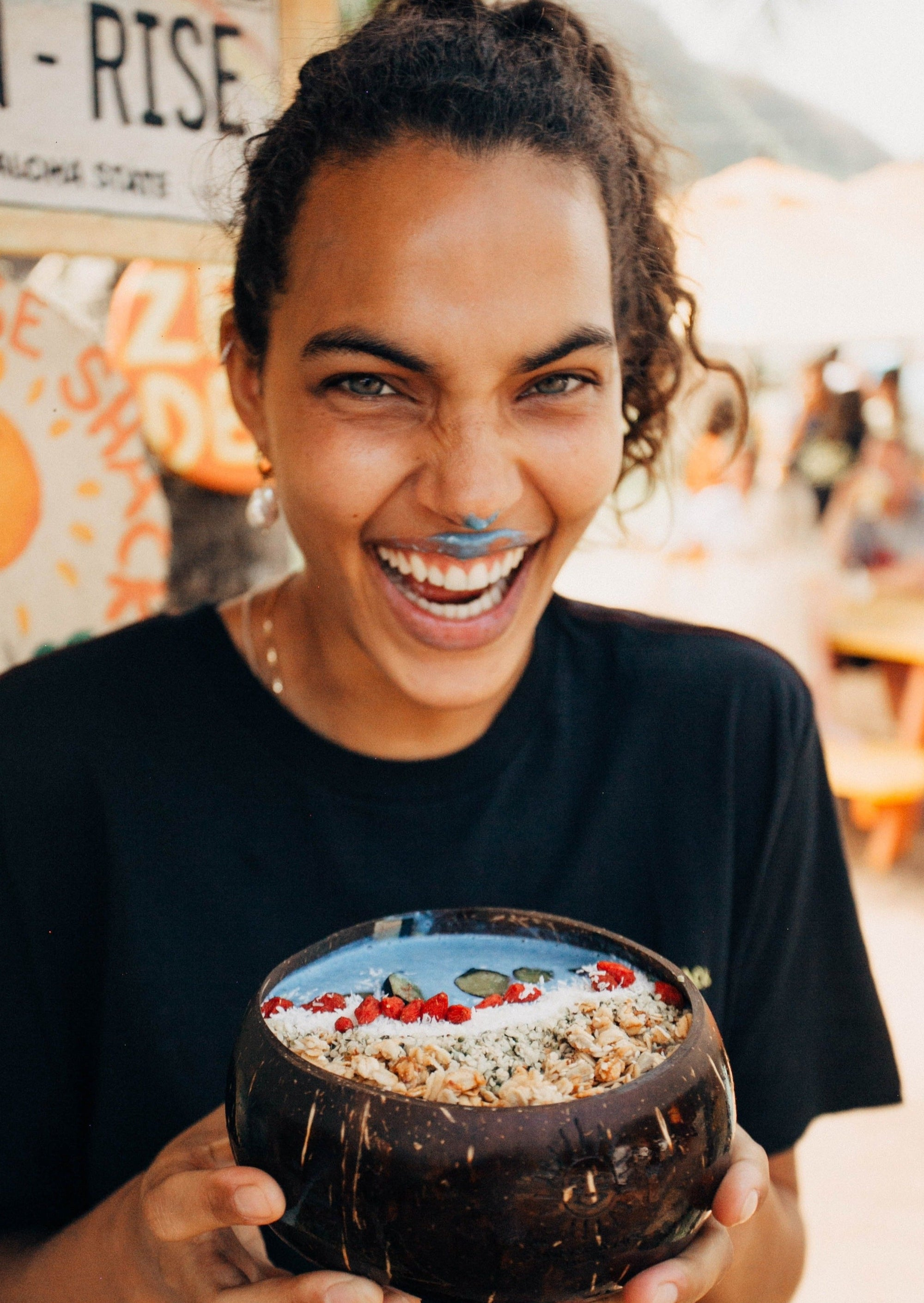 smiling woman holding coconut bowl