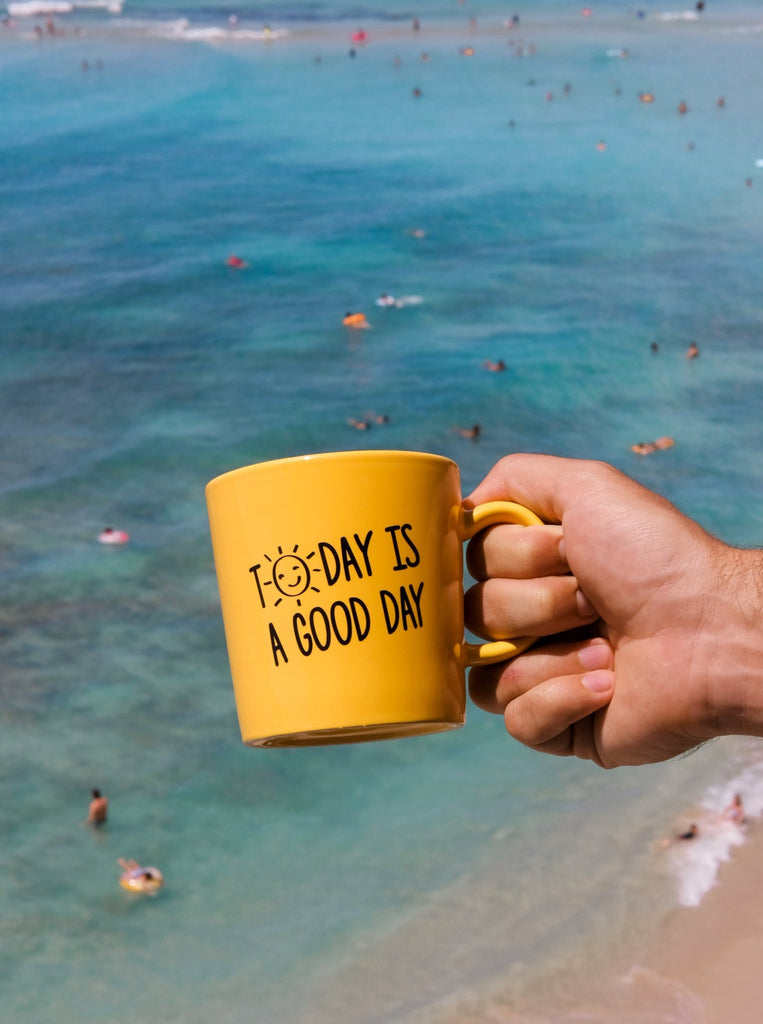"Dual sided yellow mug reading ""The Sunrise Shack Hawaii"" and ""Today Is A Good Day Mug"" featuring smiling sun"