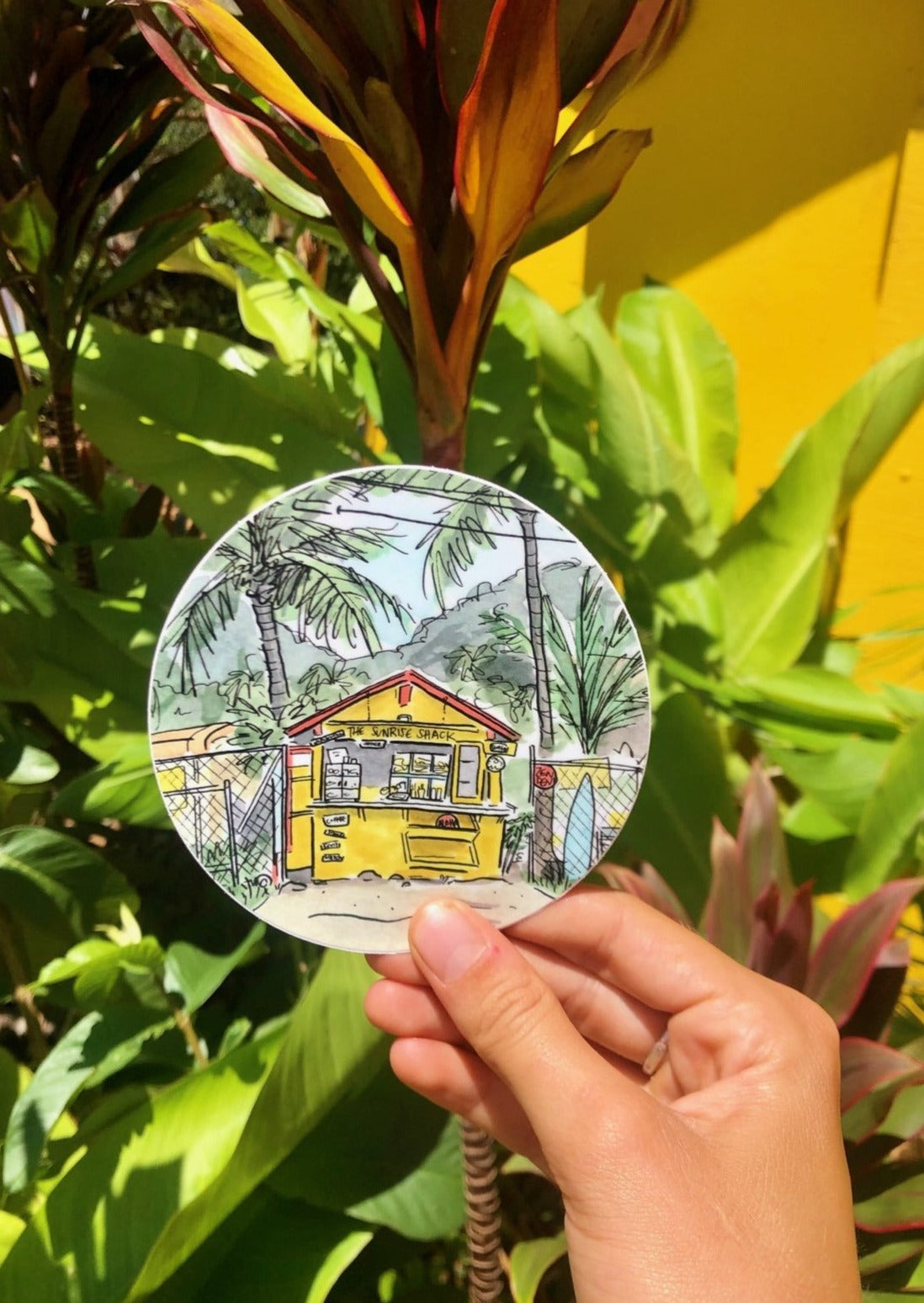 A sticker featuring a beach shack and palm trees