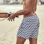 Atheletic Man in Blue Striped Swim Trunks Playing Beach Games