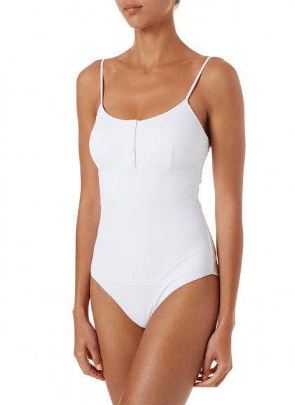 Tan woman modeling minimalist swimwear in white