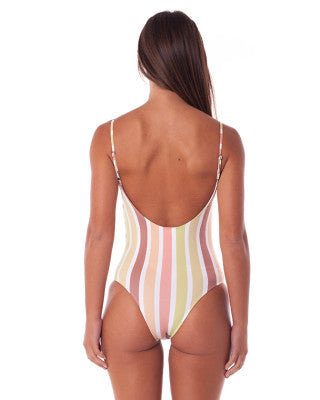 tan woman wearing multicoloured striped swimsuit