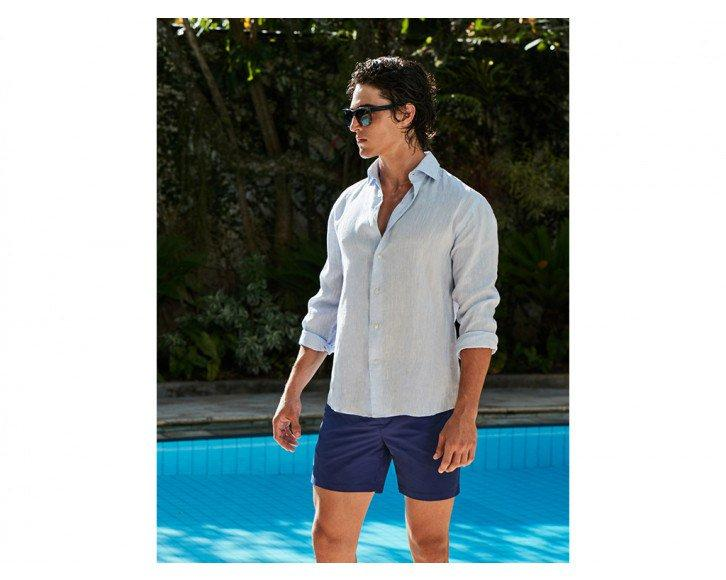 attractive man wearing a light blue linen shirt by the pool