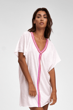 tan woman wearing a Mini Beach Cover Up Dress in White with pink trim