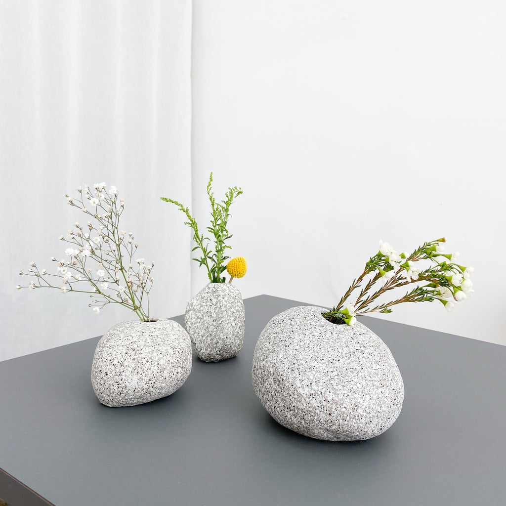 3 stone shaped ceramic vases with dry flowers inside