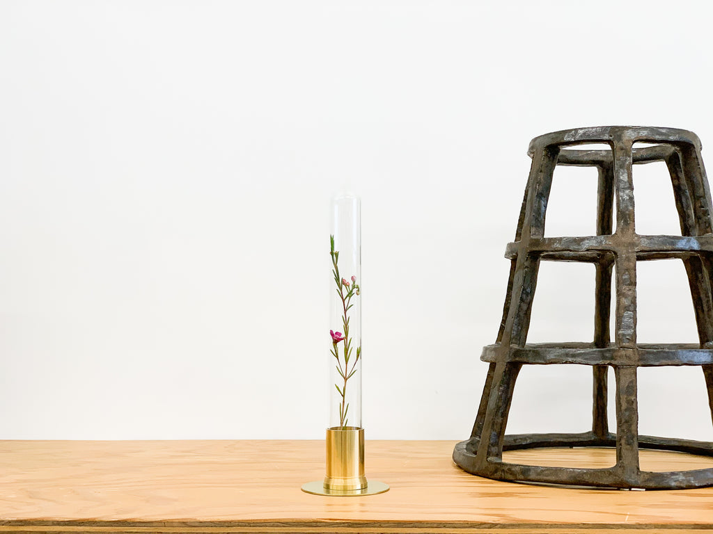 Brass container holding a single dry flower side by side with a metallic ceramic sculpture