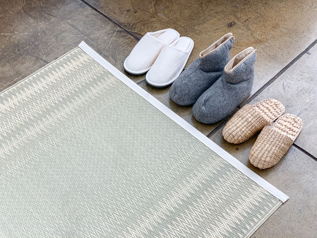 Three pairs of slippers lined up against a tatami mat