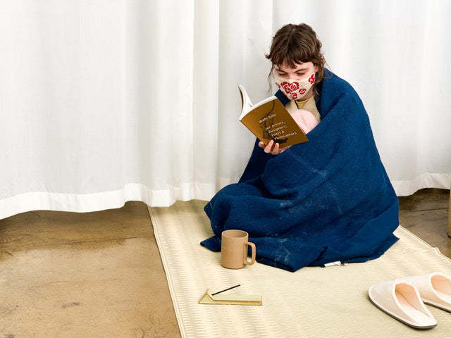 Girl reading on tatami mat with slippers, incense, tea, wrapped in blanket