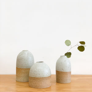 A cluster of Tomoro Morisaki's organic and rounded bud vases with dry leaf