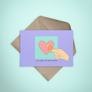 Greeting card designed by Hybrid Pencil with a broken heart and a band aid on top. Available in Lagos, Nigeria.