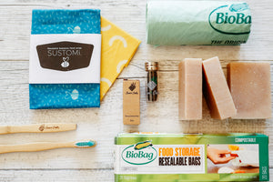 Eco friendly products flat lay soap bamboo toothbrush eco floss beeswax wraps corn starch bin liners bags