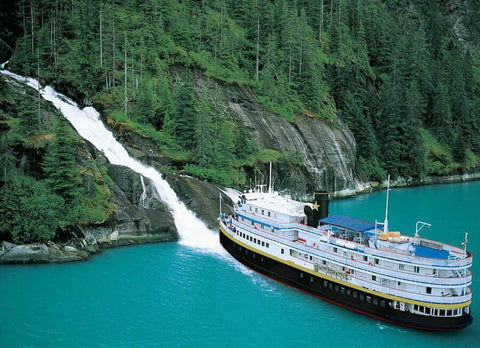 UnCruise cruise boat SS Legacy near waterfall in Alaska