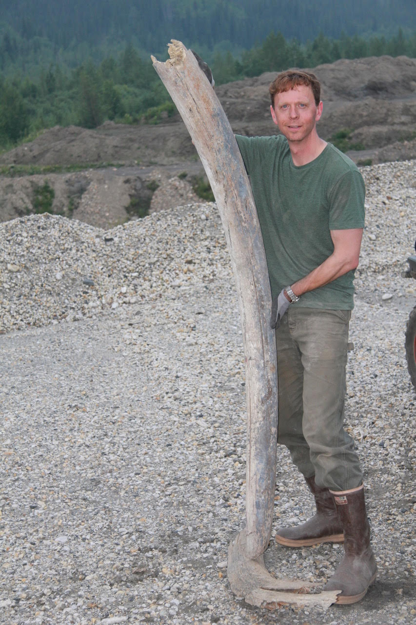 Bruce Schindler holding a mammoth tusk in the Yukon, Canada