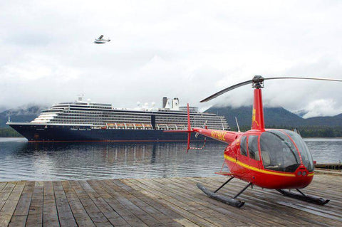Helicopter Air Alaska parked on the dock as a cruise ship goes by in Ketchikan, Alaska
