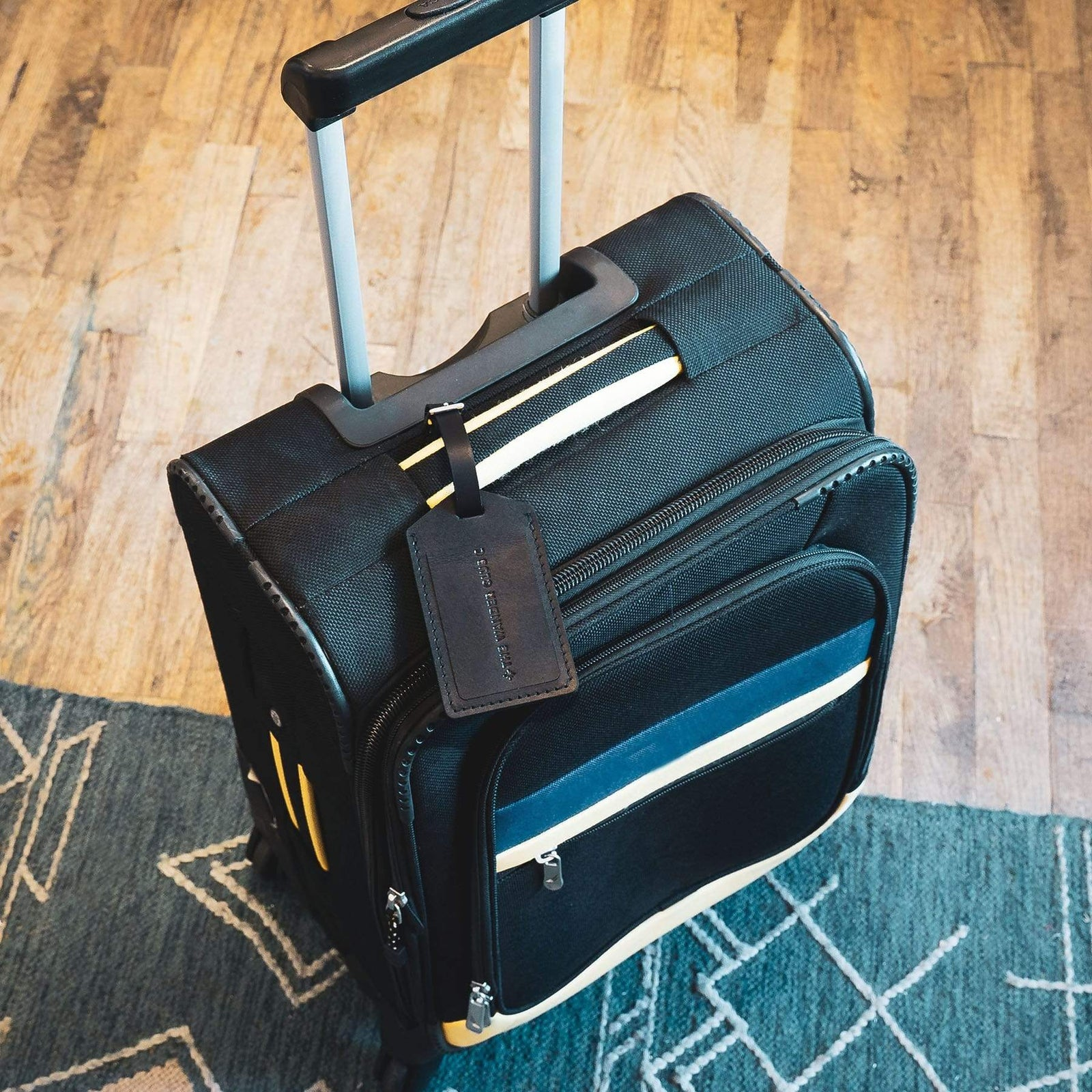 Black luggage tag on suitcase from The Wander Club