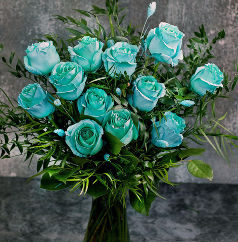 Sky blue roses; turquoise roses bouquet in a glass vase