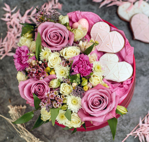 Pink flowers in a box; flowers with cookies in a box