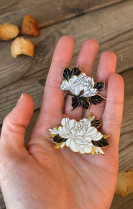 Floral enamel pins on hand, made by Lu Loram-Martin