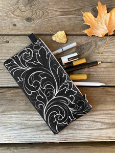 Black fabric Pencil case with white ornamental linework pattern. Lying on wooden boards with dried leaves. Made by Lu Loram-Martin, Tattoo artist, Toronto