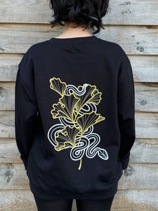 Lu Loram-Martin is wearing a black sweatshirt with a gold and white illustration of a snake amongst gingko leaves