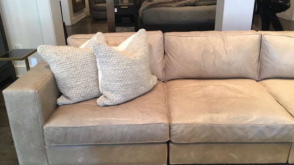 Tan Leather Sofa with two throw pillows neatly arranged in the left corner