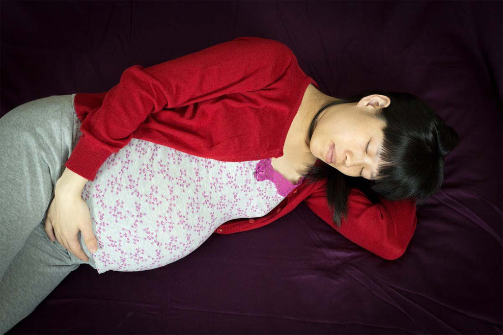 pregnant woman sleeping on side to ease lower back pain