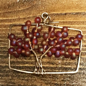 Maple colored drop glass beads and several strands of sterling silver wire twisted to form the tree of life pendant.