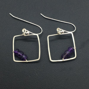 facted amethyst wire wrapped in the corner of the square frame