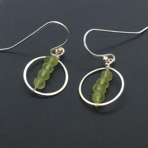 3mm faceted peridot stacks centered on a sterling silver hammered circle frame.