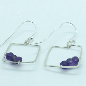 three faceted amethyst stones 3/4 of an inch square