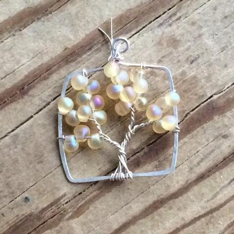 Several strands of sterling silver wire twisted to form the tree of life pendant accented with yellow glass drop beads