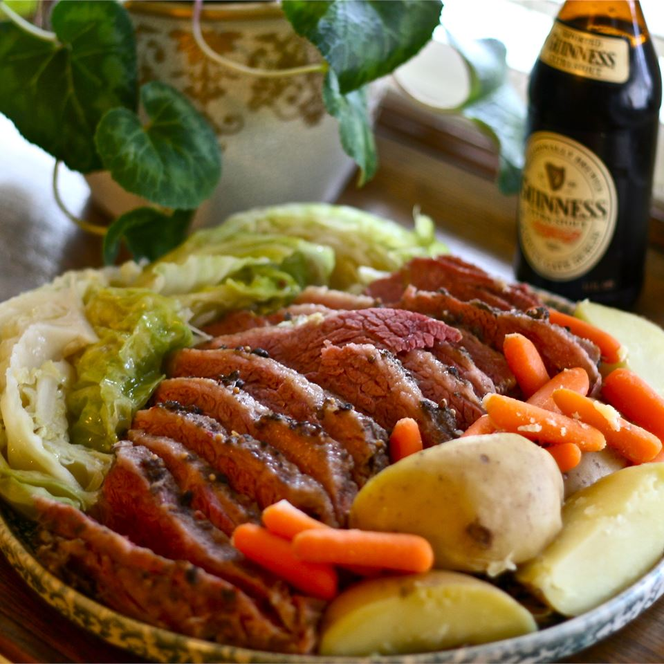 Corned beef, cabbage, and potatoes on a plate, along with a bottle of Guinness. Image originally published on Allrecipes.cm