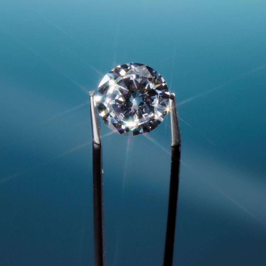 A diamond being held in tweezers.