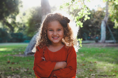 girl with curly hair and bow