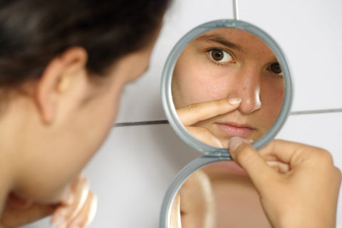Close-up of a woman looking in the mirror and popping a zit on her nose