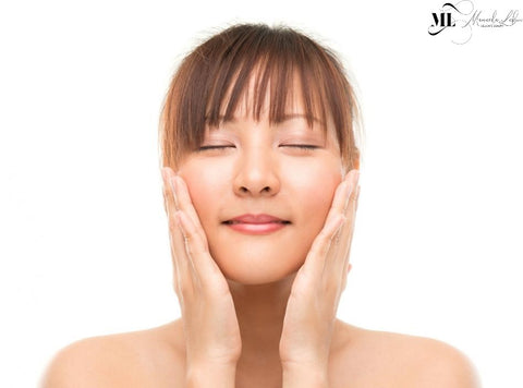 Asian girl with both hands on her face after using ML Delicate Beauty skincare products