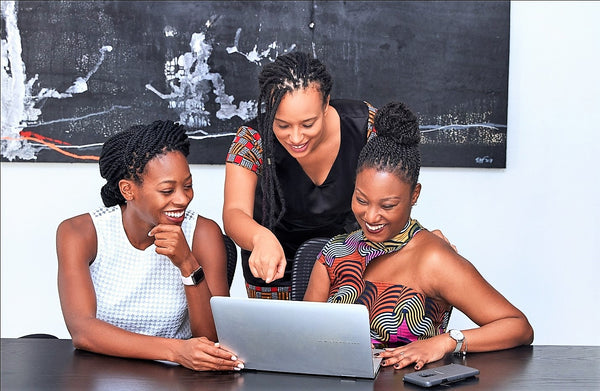Three women black-owned business owners looking at a laptop | ML Delicate Beauty